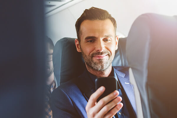 Man on an airplane looking at his smartphone