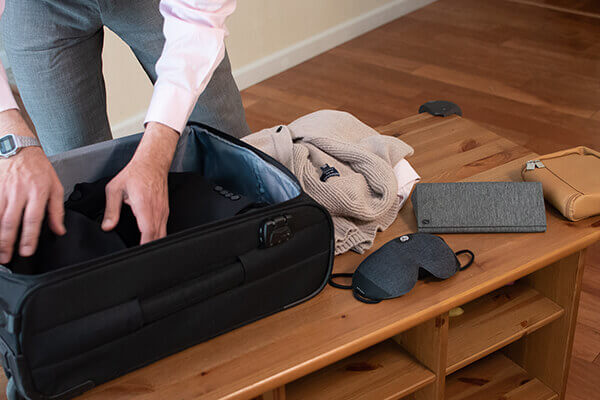 A man packing a suitcase with his Lumos Smart Sleep Mask