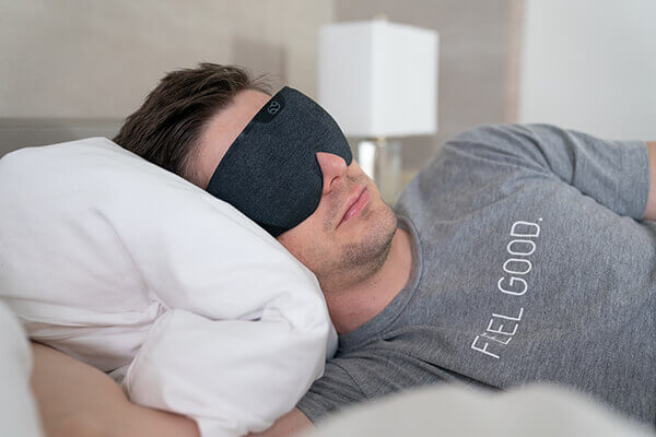 A man in a bed sleeps wearing a Lumos Smart Sleep Mask