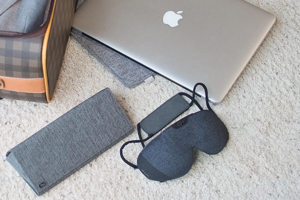 A Lumos Tech Smart Sleep Mask and travel case sit ready to be packed for travel in a nearby suitcase