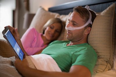 Man looks at a tablet while wearing a CPAP device in bed next to a woman